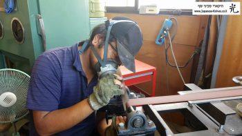 עובד מבצע גימור והחלקת פינות לסכיני שף בסדנא של שיבאטה